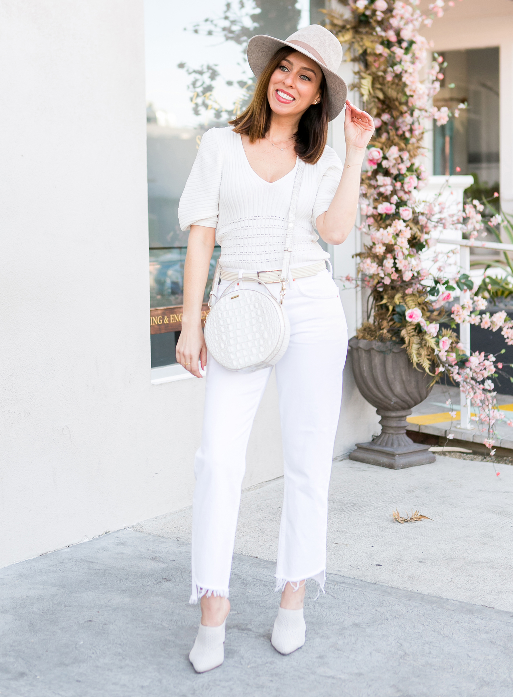 Sydne Style shows all white outfit ideas for spring in grlfrnd jeans
