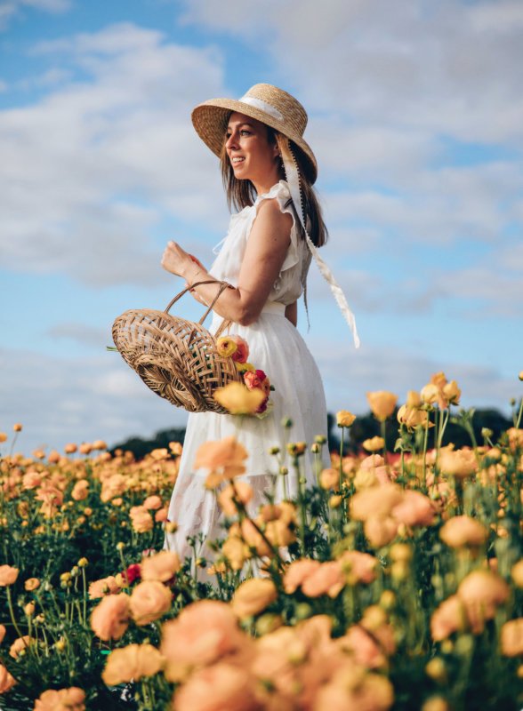 Sydne Style shows the best straw ribbon hats for summer in white dress in flower fields with ranculas