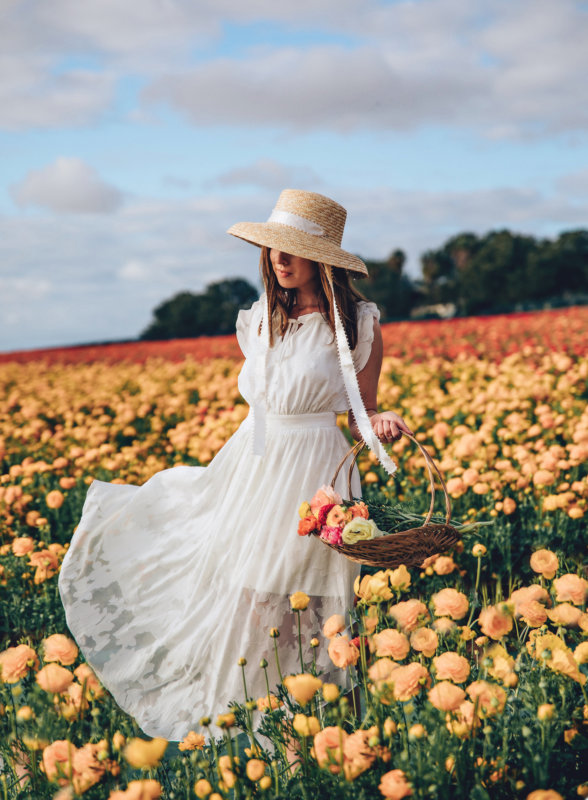Sydne Style wears white dress and straw hat in flower fields california