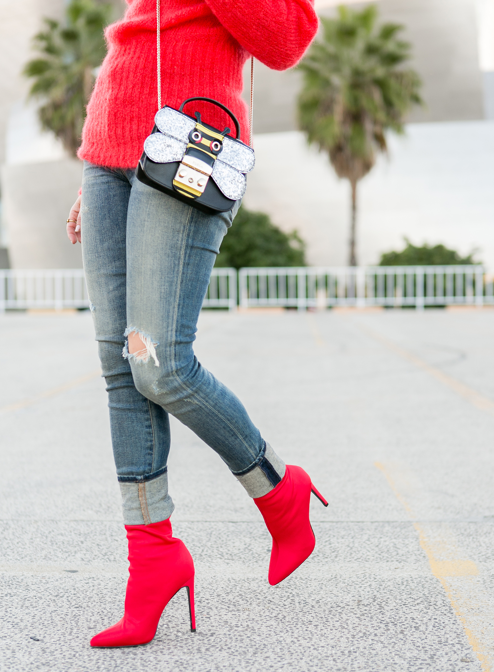Sydne Style shows how to wear the sock boots trend in steve madden red booties and la furla bee bag