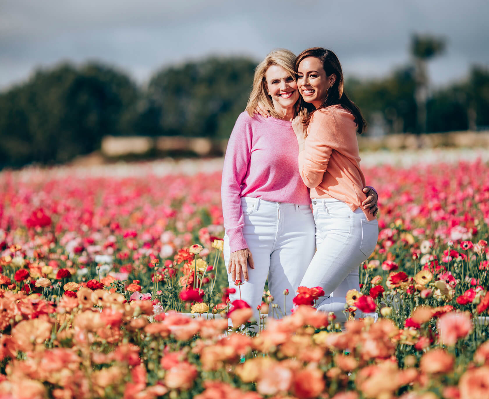 Sydne Style shows colorful sweaters with white jeans in flower fields