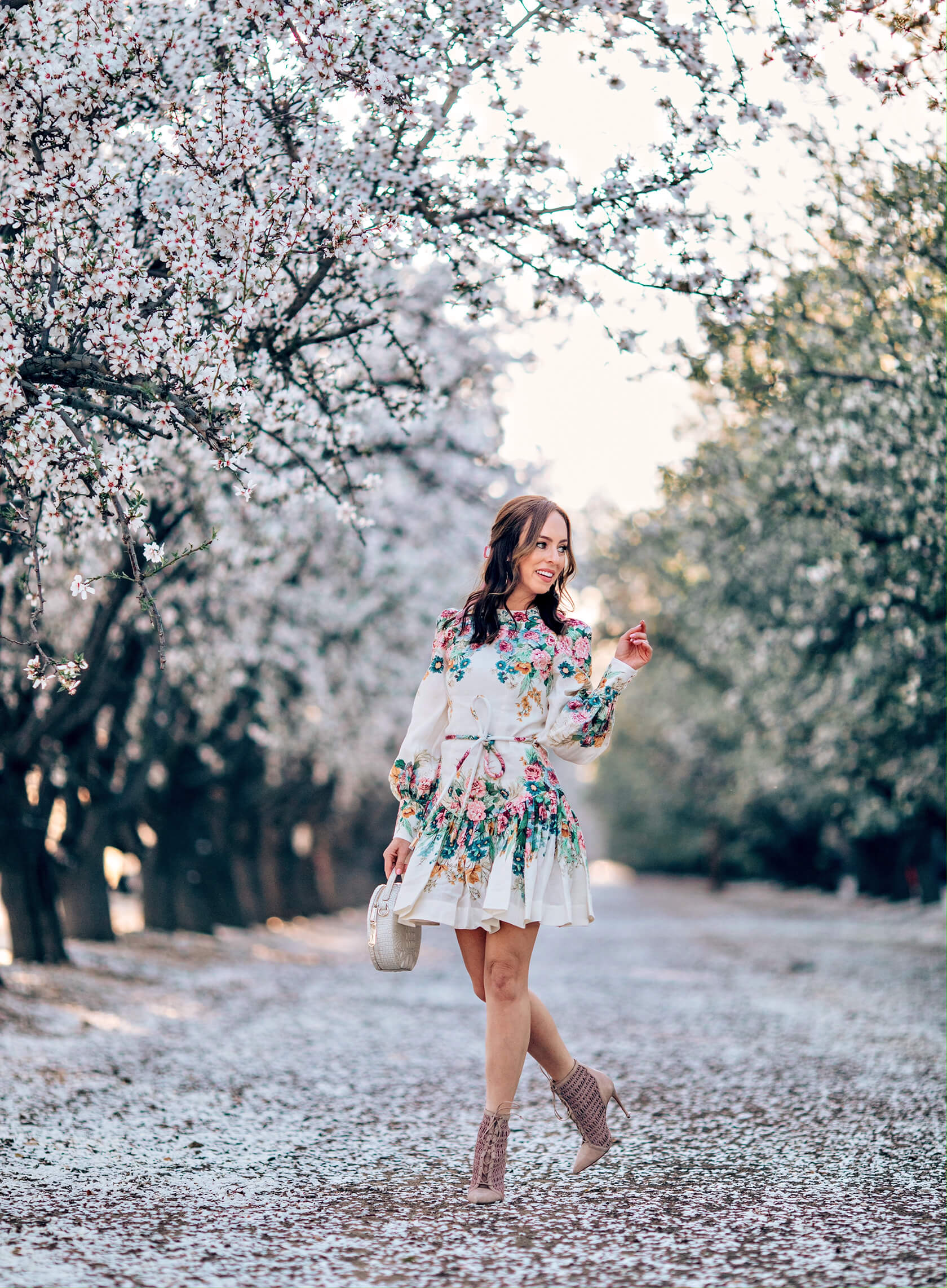Sydne Style wears floral dress and booties in almond orchards in bakersfield